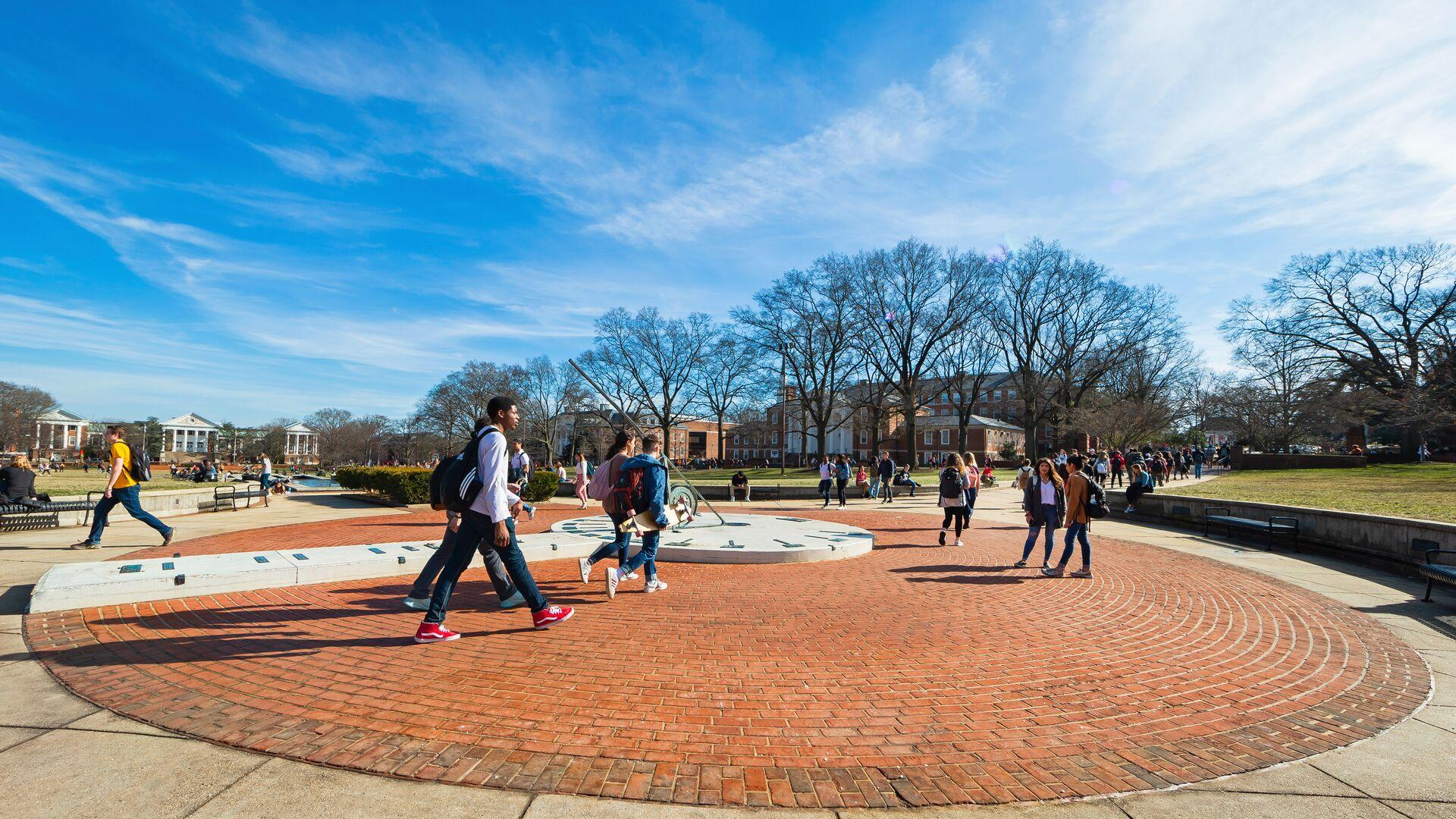 A view of the Sundial on the Mall with student activity on an unseasonably warm winter day.
