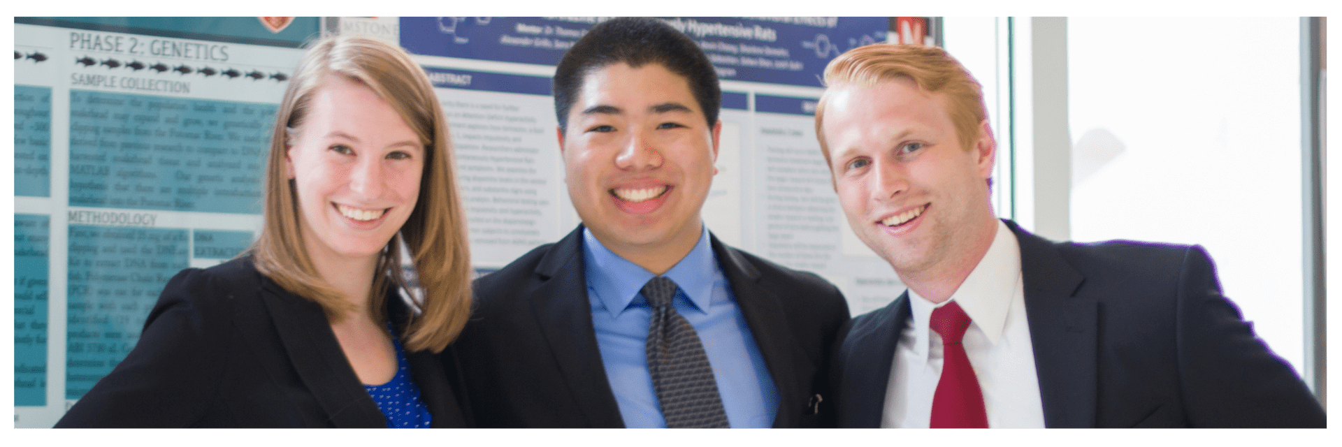 three students in business attire pose at thesis conference