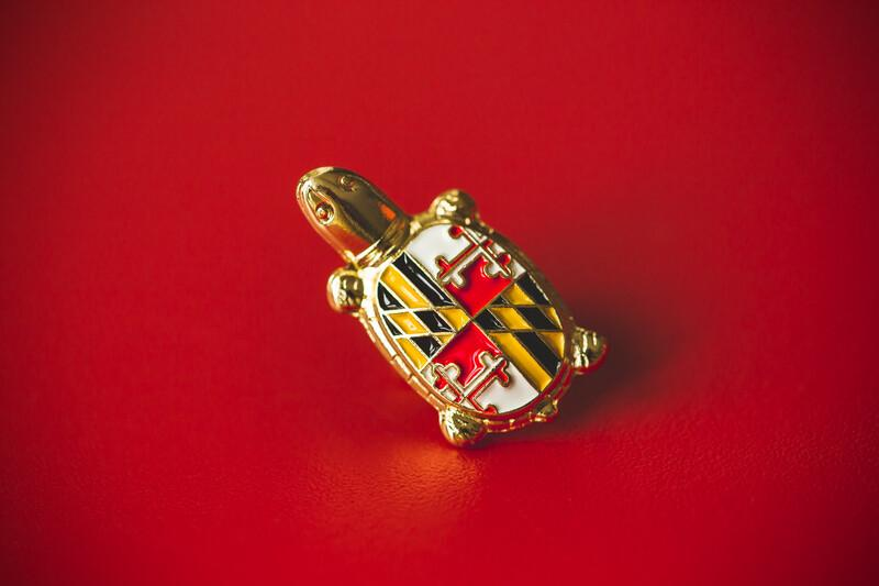 President Darryll J. Pines turtle pin with the Maryland state flag shell design against a red backdrop.
